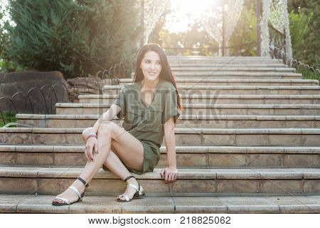 Young attractive woman in green dress sitting on stone stairs in nature and smiling in sunlight. Concept of modern healthy woman