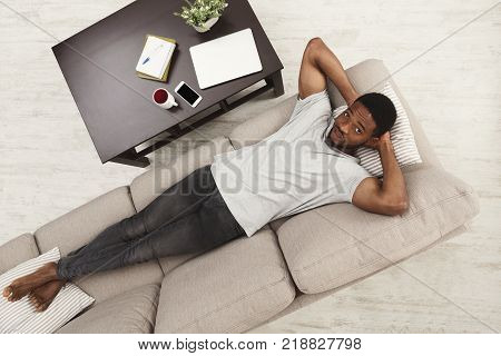 Time to relax. Handsome young african-american man in casual holding hands behind head while dreaming on the couch, top view