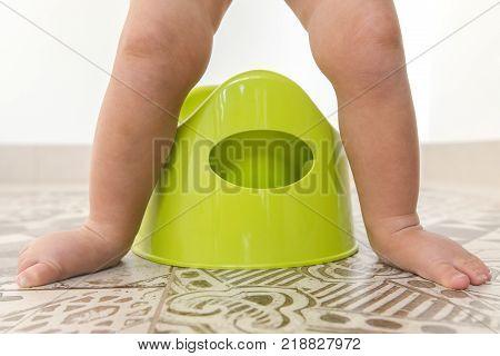 Crop the children's legs over the pot. Children's legs stands a chamber-pot.