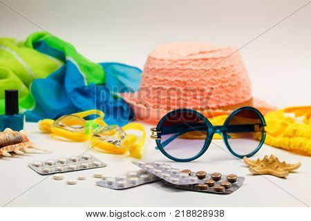 Summer women's beach accessories for your sea holiday and pill on white background. Concept of medication required in journey.