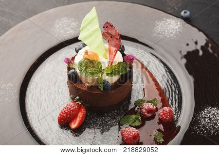 Exquisite restaurant mousse dessert. Chocolate and vanilla souffle on walnut biscuit served on glass plate finely decorated with fresh berries and mint. Exclusive meals and haute cuisine concept poster
