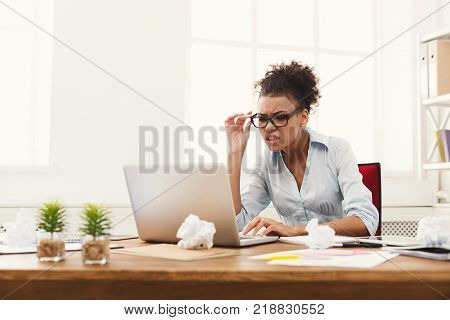 Angry business woman working on laptop at office with lots of crumpled papers on the table. Businesswoman typing something on computer while sitting at her working place, copy space