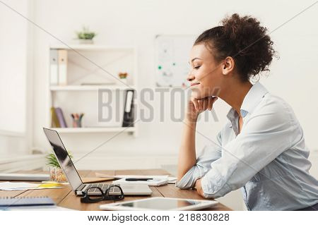 Happy smiling african-american business woman working on laptop at office. Businesswoman sitting at her working place, copy space, side view