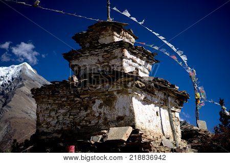 Buddhist stupa and lungta prayer flags in the Himalaya mountains, Annapurna region, Nepal