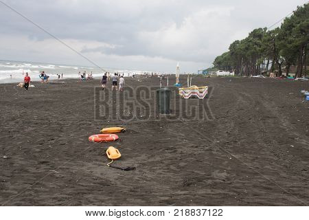 red plastic floatation rescue devices and sunbeds on beach. the weather is dull. safety vacation overcast rescue tool