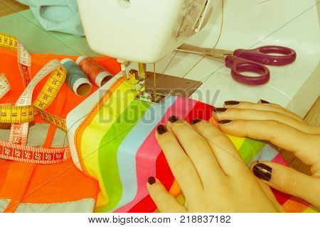 woman seamstress sitting and sews on sewing machine. Dressmaker work on the sewing machine. Hobby sewing as a small business concept. designer making a garment in her workplace - Retro color