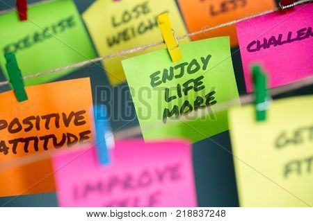 Colorful sticky notes with important life messages to enjoy life more and thoughts hanging on rope