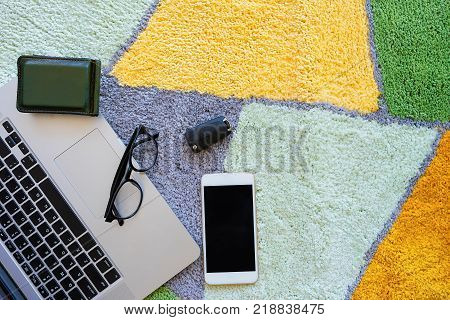Welcome home carpet with laptop,glasses,wallet,smartphone and key of car on it,welcome concept. poster