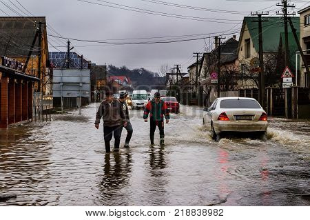 Syltse Ukraine - December 16 2017: A group of people and cars are moving along a flooded central street during a winter flood in the village of Syltse.