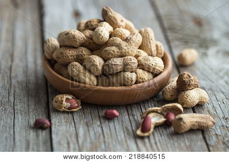 Peanut in shell texture and background. Peanuts texture. Shelled Peanuts. Healthy food. Close up view of shelled peanuts in wooden background. Abstract background and texture for designers.