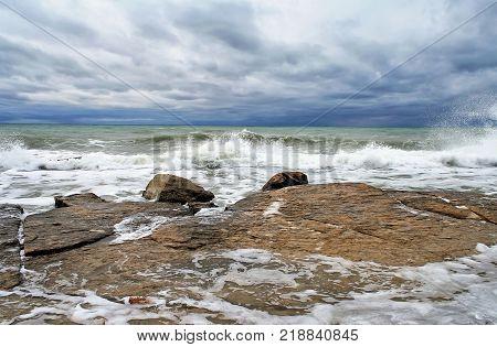 Ocean scape with waves breaking on a rocky coastline under an overcast stormy sky. Caspian Sea.