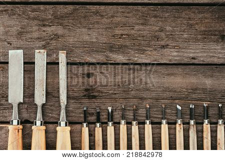 flat lay with wooden chisels for woodcraft on dark wooden tabletop