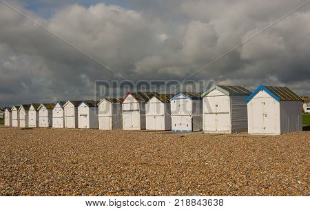 White painted beach huts on the seafront at Goring in Worthing West Sussex England