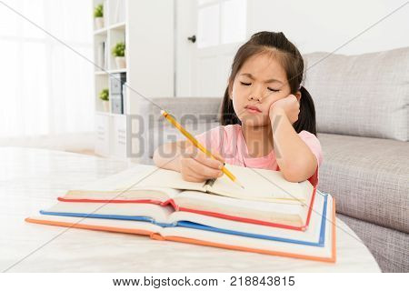 lovely pretty female little kid student looking at school textbook getting problem and feeling difficulty when she studying lesson content at home. poster