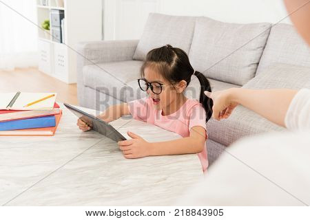 selective focus photo of mother blame little daughter using mobile pad computer playing game and school homework not finished.