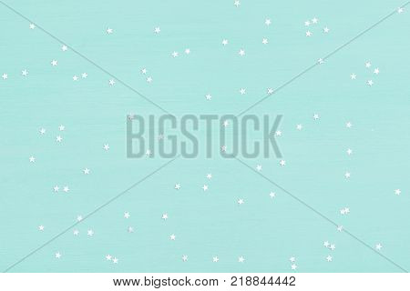 Many small shinny silver stars on turquoise wooden background