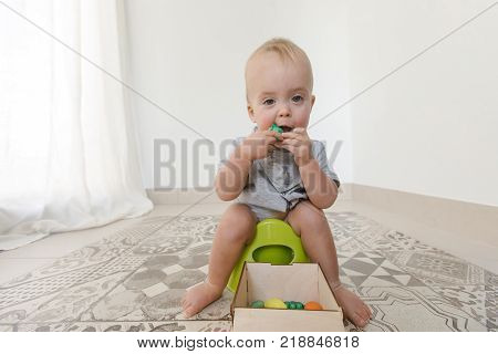 Baby sitting on potty and eating vegetables at home interior