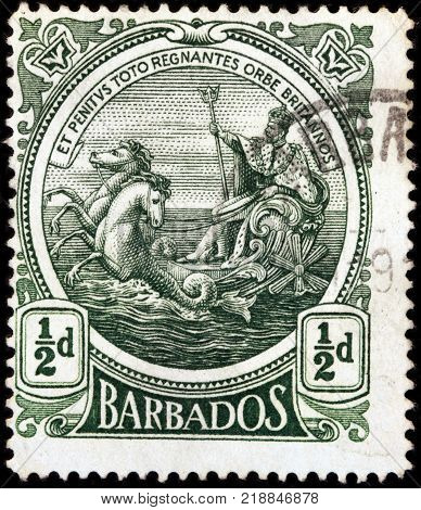 LUGA RUSSIA - OCTOBER 17 2017: A stamp printed by BARBADOS shows image portrait of George V King of England riding on a chariot across the sea and holding a trident circa 1925