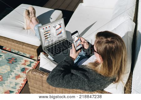 Sunny day.View from above.Young businesswoman is sitting on white couch, using laptop and smartphone with graphs, charts, diagrams on screen.Girl working, learning online.Distance work, online marketing.