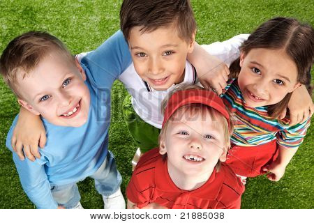 Glücklich Kindergruppe auf grünem Gras, Blick in die Kamera