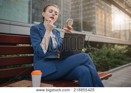 Busy woman is in a hurry, she does not have time, she is going to do make up and to work on the laptop . Worker applying lipstick in the street and working on PC at the same time. Businesswoman doing multiple tasks. Multitasking business person