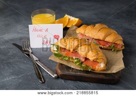 Delicious home made croissants with smoked salmon and glass of orange juice on a black background. Tasty snack. Have a nice day card.