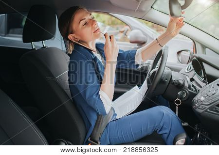 The driver going on the road, speaking on the phone, working with documents and doing a make up at the same time. Businesswoman doing multiple tasks. Multitasking business woman