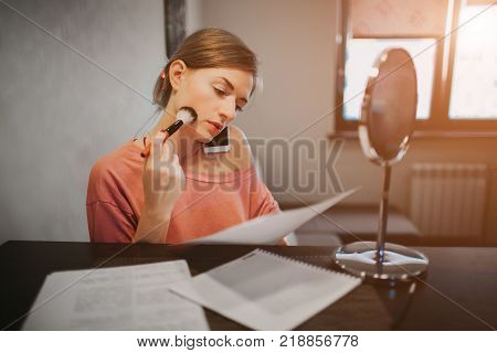 Busy woman making a make-up, talking on the phone, reading documents at the same time. Businesswoman doing multiple tasks. Multitasking business person.