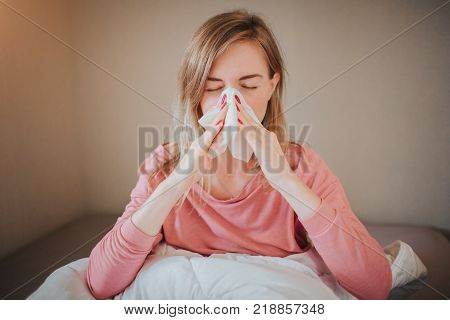 picture from a young woman with handkerchief. Sick girl has runny nose. female model makes a cure for the common cold. The patient lies in bed.