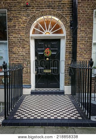 LONDON UK - 18 DECEMBER 2017: An entrance and door leading into a traditional old Georgian town house on the same street as Dickens once lived. The door is adorned with a Christmas wreath.