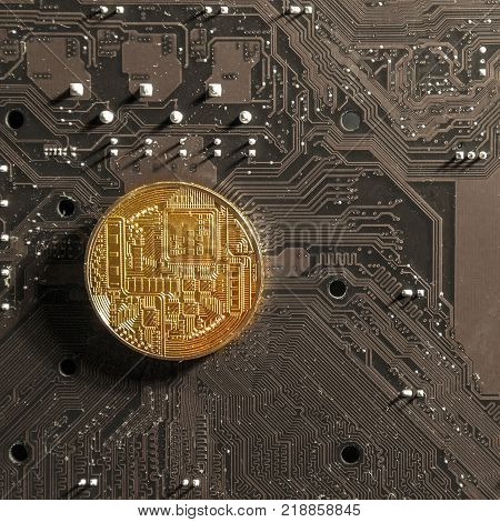 On the photo there is a gold coin of the electronic currency on the background of a computer printed circuit board. Concept mining and ICO - Initial coin offering