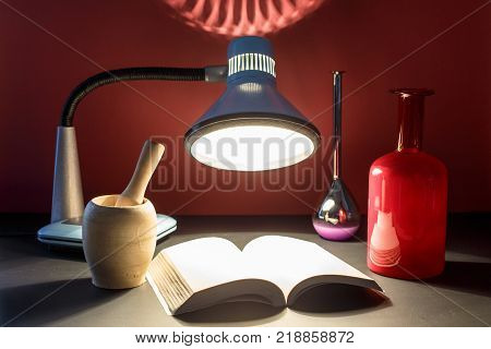 A picture is a concept of secret knowledge and magic. On the table under magical light an open book with secret texts and bottles with a magical potion.
