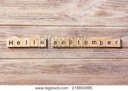 hello September word written on wood block. hello September text on table concept.