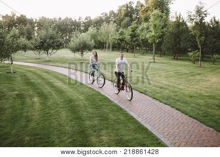 A picture with young boy and girl was made from another angle in green park. Happy couple is riding their bikes on a small road through the meadow. They are coming closer and closer.