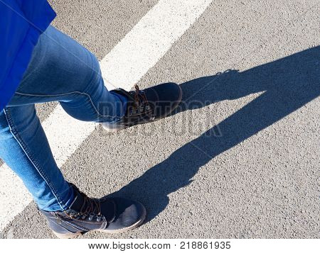 The legs of the girl in jeans and boots give a shadow on the asphalt. Interesting geometry.