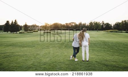 Nice picture of two people - man and woman - standing together and holding each other to the hand and looking to the sunset. They had a nice day-off in park. But now it's time to go home.