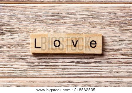 love word written on wood block. love text on table concept.