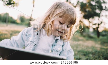 Cool and small blonde is sitting on the grass alone in the park and holding a tablet in her hands. Smart kid knows how to handle with this big bulky thing and find cartons on it. That's why she is looking on the tablet's screen. Close up. Cut view