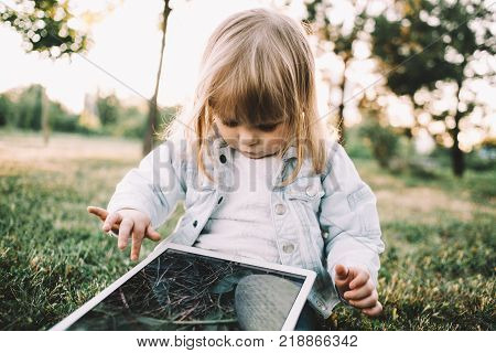 This cutie is sitting on the small meadow near trees and holding a huge laptop on her knees. This bulky gadget coveres all of her legs. Despise that the girl is looking to tablet's screen that shows beautiful picture of grass on it. Close up. Cut view