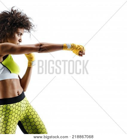 Boxer woman in yellow bandages making direct hit. Photo of sporty african woman during boxing on white background. Dynamic movement. Side view
