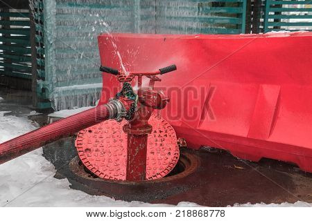 Open water intake well and fire hydrant. Jet of water escapes from the faulty tap
