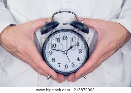 Doctor with alarm clock in hands it is time to make an appointment for your next medical exam