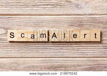 Scam alert word written on wood block. Scam alert text on table concept.