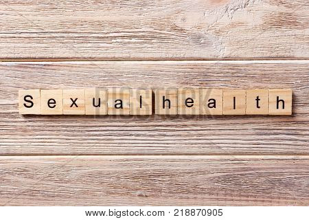 Sexual health word written on wood block. Sexual health text on table concept.