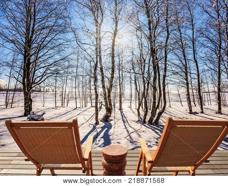 Comfortable wooden chaise lounges for relaxing in forest. Sunset in the Arctic. The sun shines low over the horizon. The concept of extreme and ecotourism tourism