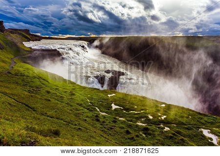 Fantastically picturesque waterfall in Icelandic tundra - Gullfoss. Huge masses of water crash into the abyss. Water fog fly up over falls. The concept of extreme and phototourism