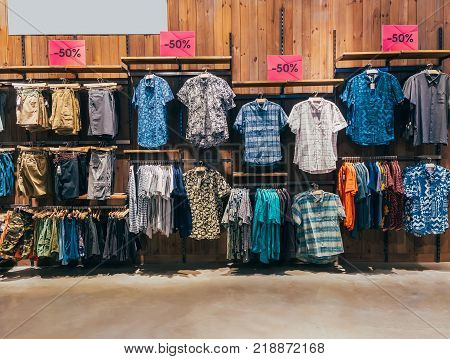 Row of colorful man apparel on shoulder hangers of at boutique in mall. Clothes hanging on rack. Set of casual male fashion on wooden hanger. Wardrobe showcase 50 percent discount.