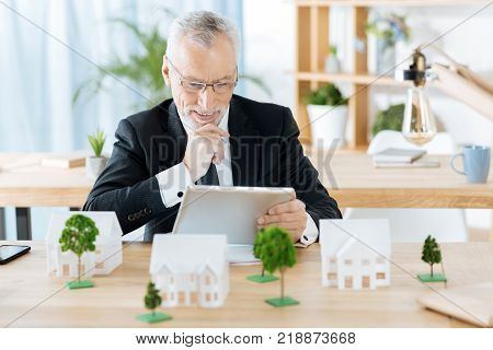 Rather interesting. Positive emotional enthusiastic real estate agent feeling happy while sitting at the table covered with miniatures of houses and looking at the screen of his modern tablet