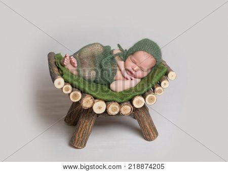 Sleeping newborn baby on wooden crib.