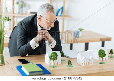 Serious glance. Concentrated busy responsible real estate agent feeling nervous before seeing his clients while being in a light comfortable office and looking at the miniature houses on his table